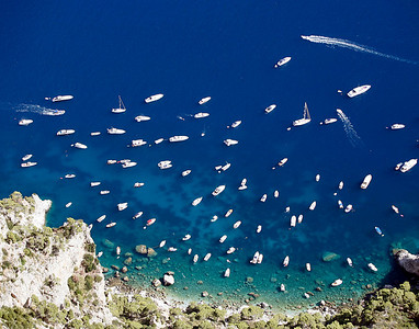 Boats float in the azure blue waters near the Blue Grotto at the Isle of Capri, Italy.