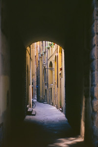Arch leading into a narrow street in Florence with bicycles, doorsteps and flower boxes;