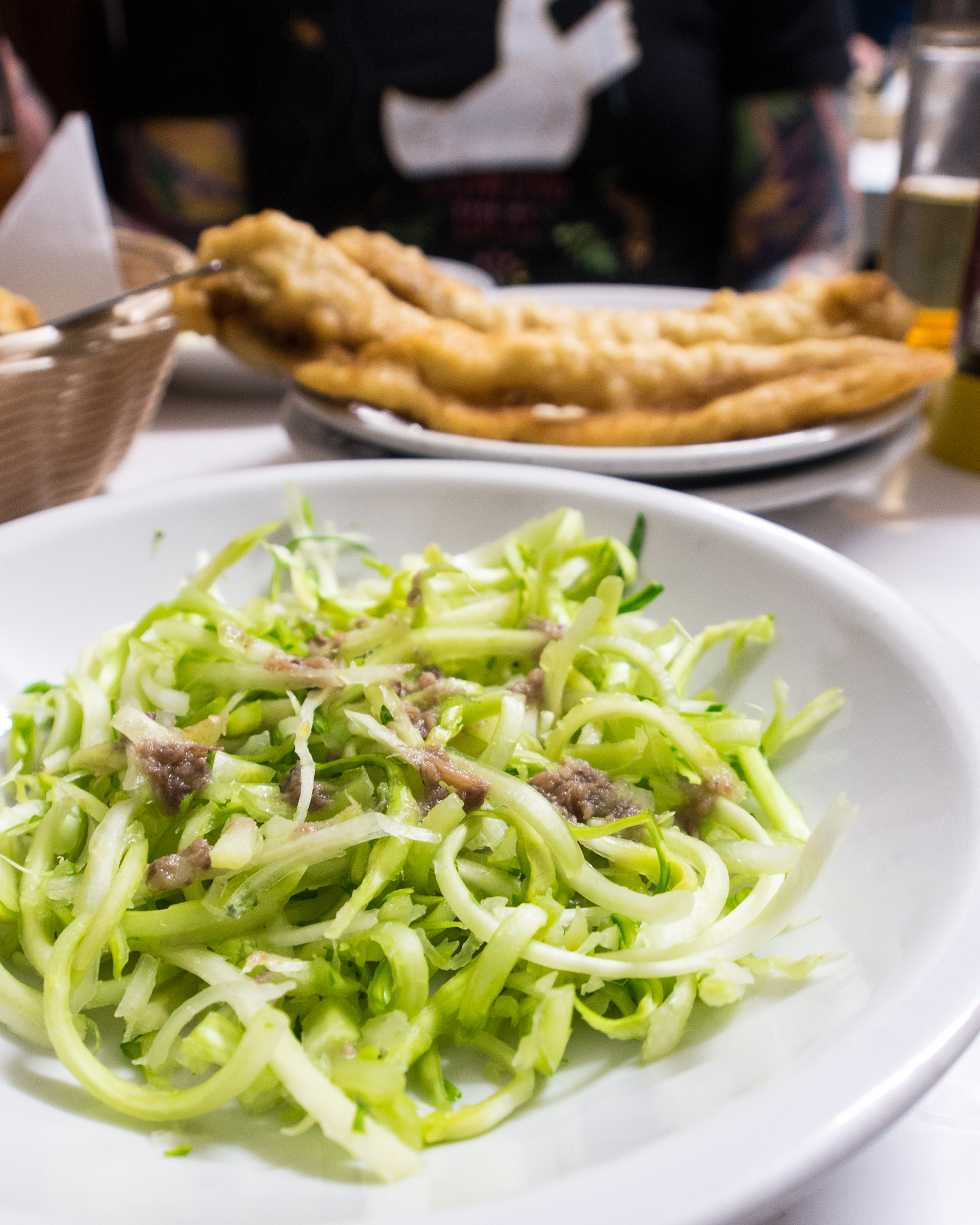 Italian puntarelle salad in a white bowl made from chicory.