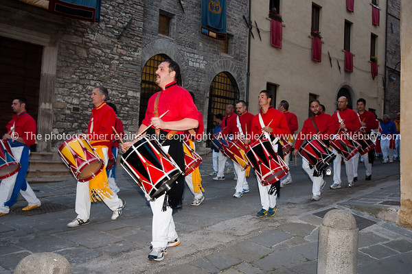 Dressed in colours of their patron saints, the people of Gubbio fill the streets marching and celebrating. Crowd on Palazzo Grande, Gubbio.  Italian images.