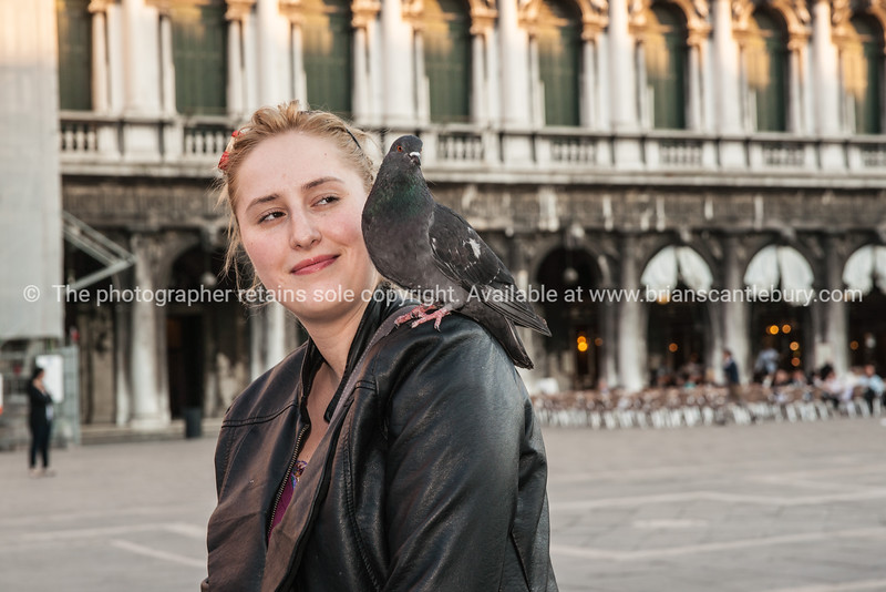 Pigeon lands on girls shoulder.