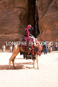 Camel rider in front of gorge that is entrance to TREASURY.
