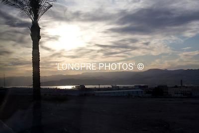 AQABA, JORDAN sun setting across sea and Sinai Peninsula.