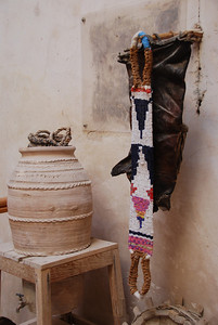 The woven belt is used to support someone as they climb up a date palm, the leather bag to collect the dates is hanging behind it.