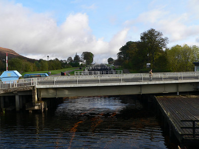 """Crossing the swing bridge, built in 1901, over the Caledonian Canal. The series of eight locks, known as Neptune's Staircase, give access to the higher sections of the canal. Engineered by Thomas Telford and opened in 1822, the canal links the east and west coasts of scotland via the Great Glen and Loch Ness."""