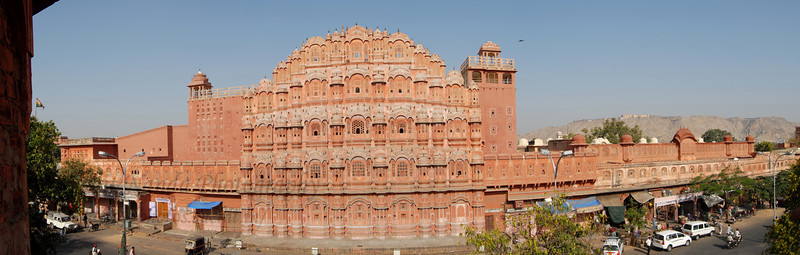Panoramic image ofThe Hawa Mahal (Palace of Winds)  Hawa Mahal is one of the Jaipur's major landmarks, although it is actually little more than a facade. Built in 1799, this five-storey building which looks out over the main street of the buzzing old city is a stunning example of Rajput artistry with its pink, delicately honeycombed sandstone windows, of which there are 953. It was originally built to enable the women of the royal household to watch the everyday life and processions of the city. The palace was built by Maharaja Sawai Pratap Singh and is a part of the city palace complex.