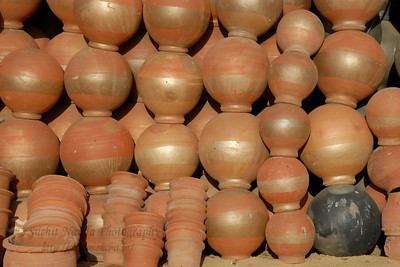 Odd one stands out. :)  Pots and other terracota products being sold on the streets. Street view of Jaipur, Rajasthan, India.