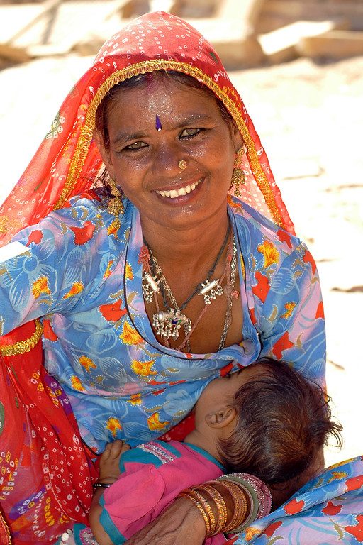 Street shot of a mother feeding her child at the Jaisalmer Fort, Rajasthan, India. South Asia.