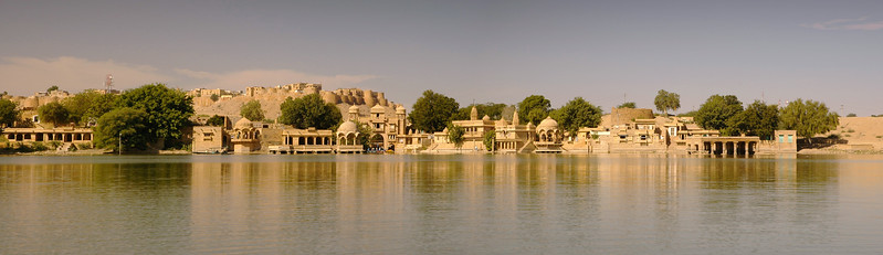 Panoramic image from Gadisar lake of Jaisalmer Fort.  This tank outside the city walls, once held the town's water supply, and, befitting its importance in providing precious water to the inhabitants of this arid city, is surrounded by small temples and shrines. A wide variety of waterfowl flock here in winter. The tank was built by Maharaja Gadsi Singh, taking the advantage of a natural declivity that already retained some water. Tourist often do boating here.