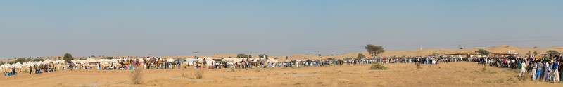Panoramic view of Jaisalmer Desert Festival - camel races, polo matches, puppeteers, jugglers, men with long mustache, turban tying competitions, locals dressed in colorful traditional dresses. Sam desert near Jaisalmer, Rajasthan, India.