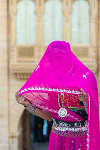 Traditionally dressed Rajasthani lady usually cover their heads (ghunghat) as a mark of respect and shyness particularly in front of non-family men or elders. Jaisalmer, Rajasthan, India.