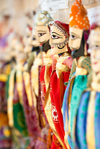 Kathputli (Puppet). Rajasthani string puppetry is vibrant and thriving. These handmade wooden puppets are much more than just plaything or decorative dolls. They are a part of the traditional performance of puppetry – narrating an event from history, myths, folklore or legend, complete with music and speech. They are the repository of traditional wisdom, knowledge and social mores. Within them are contained the oral history of the region.  The tradition of handmade string puppets of Rajasthan is more than a thousand years old. It is known as 'Kaathputli' ('kaath' means wood, and 'putli' is puppet, i.e. wooden puppet) and mainly practiced by the Bhat community. Jaisalmer, Rajasthan, India.