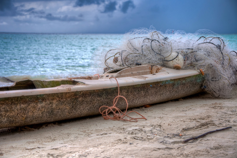 """I noticed what looked like an abandoned boat that I thought was really interesting. When I stopped for a few pictures of it, I quickly found out that it wasn't abandoned. The picture was totally worth the harrasment from the group of guys who """"owned"""" the boat."""