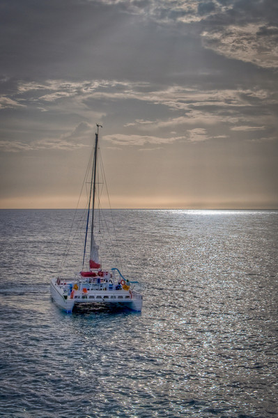 We were at Rick's Cafe in Negril as the sun was setting. I caught this scene of a sailboat off the bay as the sun peeked out from the clouds.