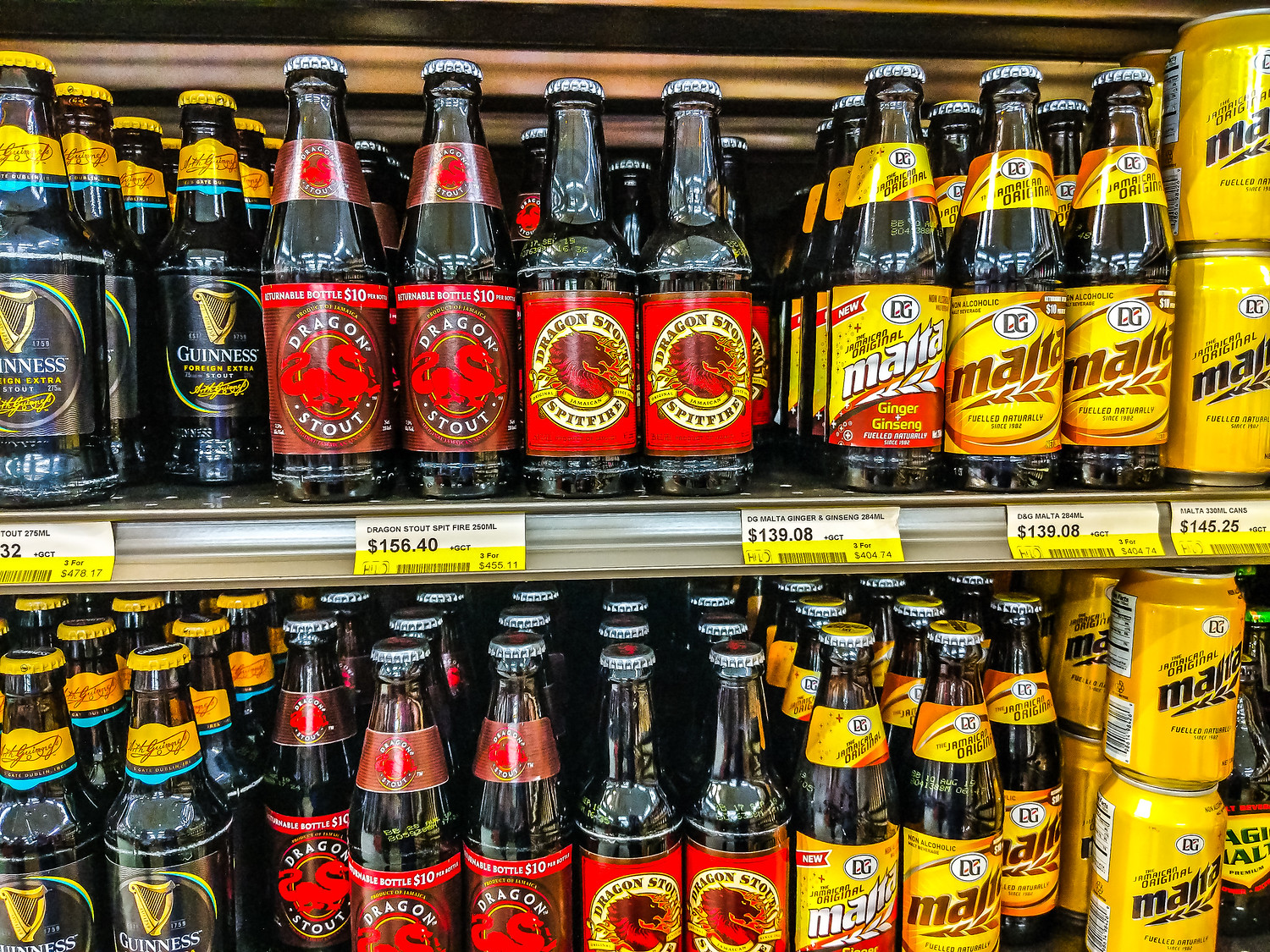 Drinks in Jamaica on a supermarket shelf including Guinness Foreign extra beer, Dragon Stout and non-alcoholic malta.