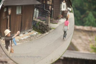 Seen in a convex mirror, a woman takes a photo in Shirakawa, Japan.