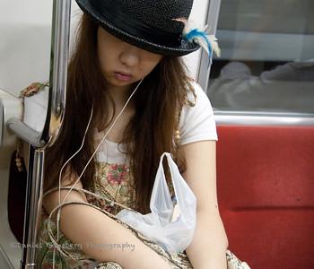 A woman takes nap aboard a Tokyo subway.