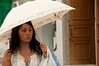 A young woman stands under an umbrella in Tokyo, Japan.