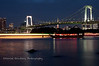 Boats at night in front of the Rainbow Bridge, as seen from Odaiba, Japan. The streaks of light come from a slow exposure.