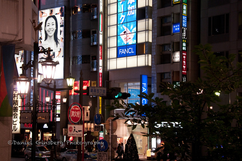 The Ginza district in Tokyo, Japan at night, filled with neon signs.