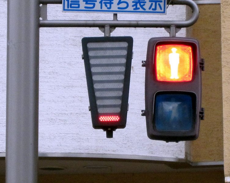 Walk/Don't Walk sign. Instead of a numerical countdown the number of red bars decreases to indicate how much time is left before the sign changes.