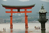 The picturesque Itsukushima (Miyajima) Shrine with a lantern in the foreground and people wading in the water.