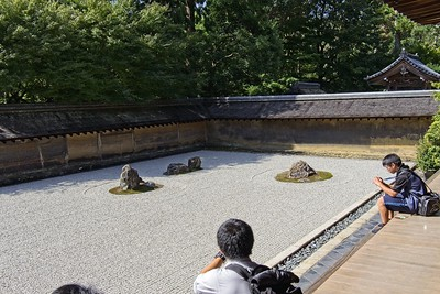 The back walls are made from clay.Viewing  the rock garden at the Ryoan-ji Temple.
