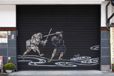 Artwork on the shutters of a closed store.