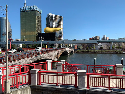 Across the Sumida River sits The Asahi Beer Headquarters with a giant flame on the roof.