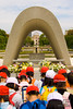 Cildren at the Cenotaph for A-bomb victims, with the Flame of Peace and Atomic Bomb Dome behind, Hiroshima