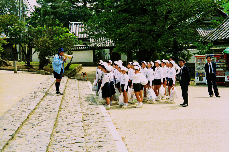 Children being organized by a teacher during a school outing.