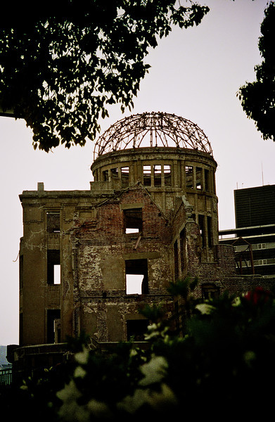 Genbaku Dome, Hiroshima<br /> <br /> Ground Zero for the end of World War II in the Pacific theatre.<br /> <br /> At the age of 19 when I took this picture I was much a stilted young man who rarely found much pathos in my surroundings.  That said, I was deeply affected most of my time in Japan and no more so than my brief time in Hiroshima.  After nearly a year living amongst Japanese families, I  changed from an American to American-in-Japan to American-Japanese, so much to an extent I was awash in a mix of emotions that straddled cultures and race and that to this day I do not think I can squarely describe to you.  I was relieved that the war had ended.  I was ashamed we had let ourselves, as a species, come to this.  I was proud that we, as Americans, had courage to stand up to the tyranny of totalitarism.  I was read enough to know history is never so simple.  I was angry with the humiliation delivered at the hands of an arrogant occupation and all that it wrought in the aftermath.  I understood the necessity of the occupation and appreciated the wisdom in the rebuilding and partnership that emerged.  History is never so simple to have a single emotion or conclusion encapsulate itself, nor were or are my emotions.  Only time has tempered them to a degree that now I see them as echos of a younger, more naive young man who shares my name with me.