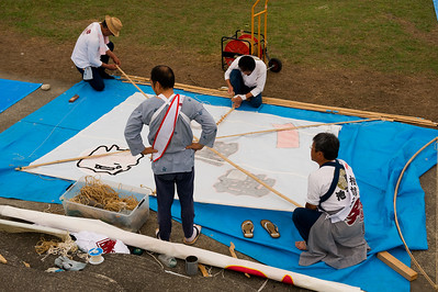 "The Hamakita kite festival is a small affair relative to the one held in Hamamatsu in May.  Although I could not read any of the signs or literature for it, it appeared that teams were given a ""pit stop"" place to build their kite."