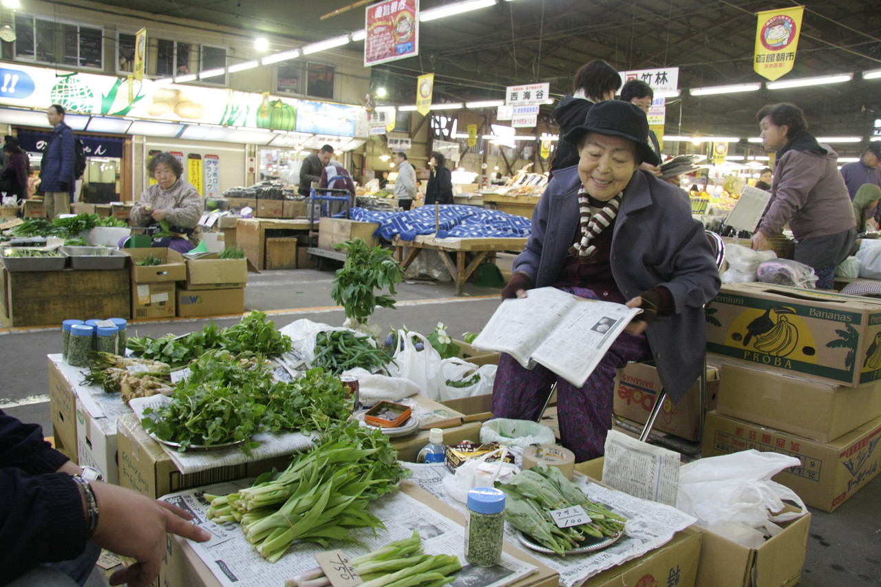 One of the many women at the morning market selling produce. Many of the vegetables are wild mountain vegetables picked from nearby.
