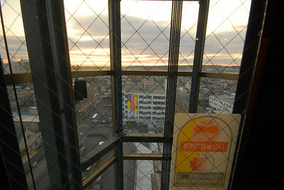 """The elevator doors are made of glass so you don't have to wait for the elevator car to see out. The sign on the door loosely translates to """"Be careful. These doors eat fingers and you'll cry like this."""""""