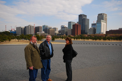 Scott, Daral, and Donna in front of the Tokyo skyline. The ground is mostly gravel and empty. On New Year's Day, all the space behind us will be filled with people waiting for the emperor to emerge and wave to the crowd.