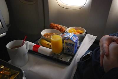 About 90 minutes before landing, the window shades are opened and the occupants come back to life. Although it is mid-to-late afternoon at our destination, it feels like early morning, so we get breakfast. Oliver here has selected cereal and fruit.