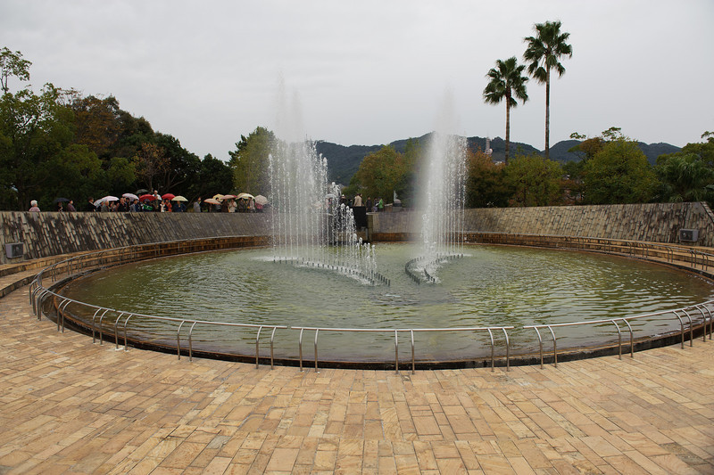 """Written on the sign near this fountain: The Fountain of Peace  When the atomic bomb exploded on August 9, 1945, thousands of people suffered terrible burns and died begging for water.  Nagasaki city and the National Council for World Peace and the Abolition of Nuclear Weapons constructed this """"Fountain of Peace"""" with donations received from all over Japan, and dedicated it as an offering of water to the victims of the atomic bomb and a prayer for the repose of their souls.  It is our ardent wish that you will remember the departed victims whilst visiting this fountain, and that you will join us in striving for world peace.""""  -Mayor of Nagasaki  The fountain sends up a sparkling spray of water in the shape of a pair of wings, evoking the dove of peace and the crane after which Nagasaki harbor has been named because of its similarity to the shape of the harbor. Completed: August 1969; Reconstructed, August 1985."""