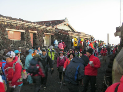 The many joyful and jolly folk at the summit of Mt. Fuji.  It is as if the summit is a small town!