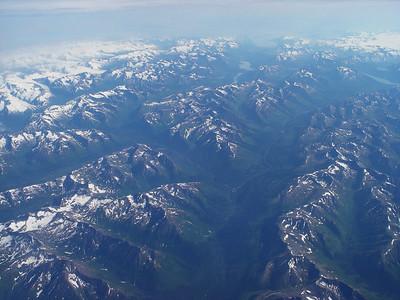 Lush valleys below snow-capped peaks.