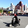 A woman pushes her motorbike past the intersection near the Kaminarimon (Thunder Gate) in Asakusa.
