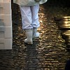 Dressed in white, a fish vendor walks along the old stone cobbles.