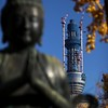 A statue at the shrine serves as a frame for the Tokyo's tallest building, still under construction.