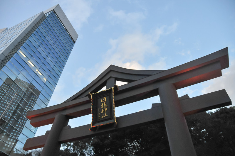 Entrance to the Hie Jinja Shrine. The Hie Shrine is a Shinto shrine in Nagatacho, Chiyoda, Tokyo, Japan. Juxtaposed with a modern skyscraper behind it.