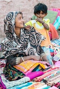 Lady with her baby selling clothing material on the streets at Ghantaghar market, Jodhpur, Rajasthan, India.