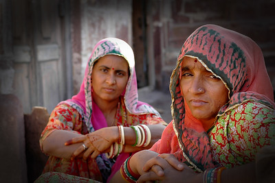 Ladies living inside the Mehrangarh Fort   Mehrangarh Fort was founded in 15th century by the Rathore Rajputs when they shifted their capital from nearby Mandore to Jodhpur.Mehrangarh appears to rise from bluff-coloured sandstone hill itself , so well built into the base that it is difficult to tell where the hill ends and the walls begin. It is approached by a series of seven gateways set at an angle so that armies could not charge them with any success. Past the gates, the fort-palace takes one's breath away . Across from huge courtyards are the set wings of palatial apartments that have been built over five centuries of bristling history.  Today, managed as a museum by the royal trust that maintains it, only some of the more spectacular palaces of Mehrangarh are open to the visitors .These consists of Moti Mahal with its pierced screen windows overlooking the coronation seat where the Rathore ruler have been ritually anointed to rule ; Jhanki Mahal , the apartment from where the zenana women would watch ceremonial events ; Chandan Mahal, where affairs of state were discussed ; the royal Darbar Takhat or throne room with its octagonal throne ; and the Rang Mahal where the maharaja would play Holi with his Zenana .Also noteworthy are Sheesh Mahal , Phool Mahal , Umaid Vilas and Maan Vilas , while a large tent seized from the Mughals in battle is spread for viewing in what has came to be referred to as the Tent Room. Jodhpur, Rajasthan, Western India.