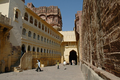 Inside Mehrangarh Fort, Jodhpur. Inside the fort, a series of courtyards and palaces greet the visitor. The palace apartments house a splendid collection of the trappings of the Indian royalty. The fort is visited by thousands of tourists every year who come to have a glimpse of the artillery system of the Rajput warriors. One can have a bird's eye view of the city from the fort. Situated at an altitude of about 125 metres, the Mehrangarh Fort is spread over an area of 5 sq. km in the heart of the city. The fort has seven gates of which the noted ones are the Jayapol, built by Maharaja Man Singh in 1806; Fatehpol or the Victory Gate built by Maharaja Ajit Singh; and the Lohapol or the Iron Gate. The 15 handprints, the sati marks of Maharaja Man Singh's widows who threw themselves upon his funeral pyre in 1843, can be seen beside the Lohapol. On the wall, one can see the strategically located cannons. Jodhpur, Rajasthan, Western India.