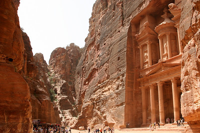 Petra - The Treasury - A view showing the small valley The Treasury is located in.  The  exit from The Siq is to the left by the people.  From here, the valley slopes gently downhill down to the right where it eventually opens out past tombs and the theatre to the city area.  This photo also shows the why The Treasury is in near perfect condition - it is sheltered from wind and rain, and hence has not eroded like many other tombs in the valley.