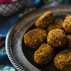 Falafel on a vintage tin plate and a salad of fresh vegetables close-up vertical