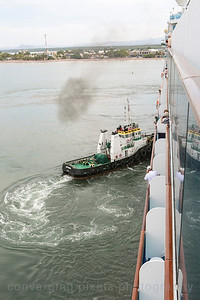 A tug steers the Island Princess into the dock at Puntarenas.